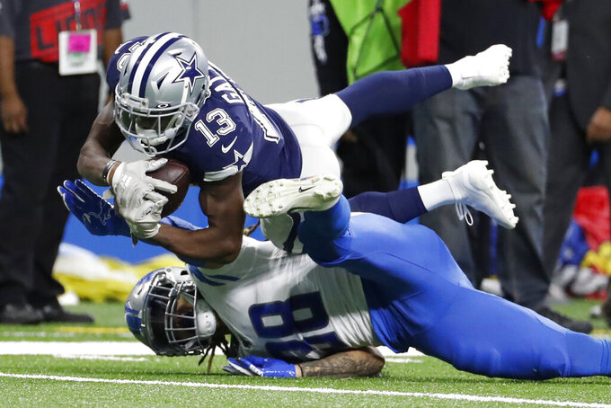 Dallas Cowboys wide receiver Michael Gallup (13) falls over Detroit Lions defensive back Mike Ford (38) after a catch during the first half of an NFL football game, Sunday, Nov. 17, 2019, in Detroit. (AP Photo/Rick Osentoski)