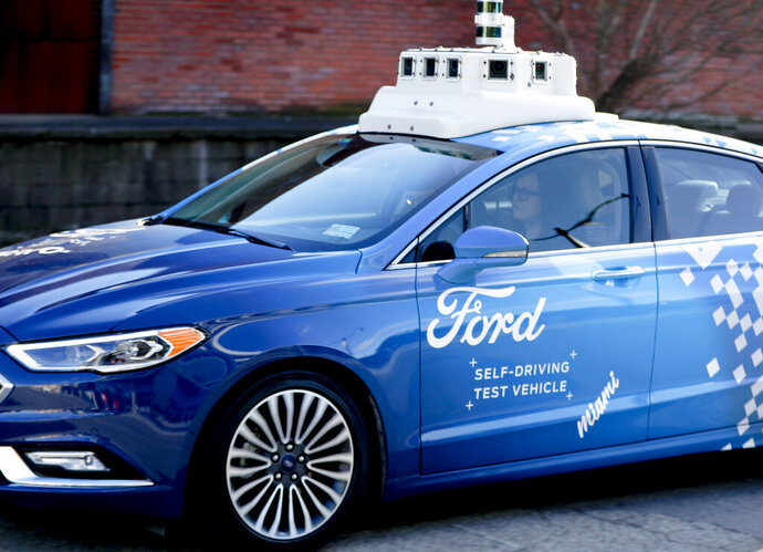 In this Dec. 18, 2018, photo, one of the test vehicles from Argo AI, Ford's autonomous vehicle unit, navigates through the strip district near the company offices in Pittsburgh. The people developing self-driving vehicles say it could be anywhere from 10 years to decades before the cars will be carrying passengers in every city. Researchers are trying to conquer a number of obstacles. (AP Photo/Keith Srakocic)