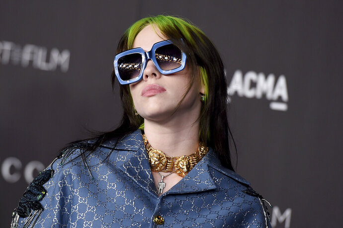 """FILE - This Nov. 2, 2019 file photo shows singer Billie Eilish at the 2019 LACMA Art and Film Gala in Los Angeles. Eilish is set to the sing the theme song for the upcoming James Bond film, becoming the youngest act to write and record a song for the iconic film franchise. Eilish, who turned 18 in December, recorded the song for the 25th Bond film, """"No Time to Die,"""