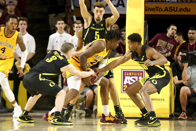 Oregon defenders Payton Pritchard (3), Chris Duarte (5) and Shakur Juiston (10) smother Arizona State's Romello White (23) during the first half of an NCAA college basketball game Thursday, Feb. 20, 2020, in Tempe, Ariz. (AP Photo/Darryl Webb)