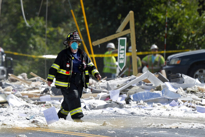 A firefighter walks through the scene of an explosion Monday, Sept. 16, 2019, in Farmington, Maine. Officials say a town's fire chief is among the injured in a propane explosion that killed a firefighter. State public safety spokesman Steve McCausland said after Monday morning's explosion at a nonprofit center in Farmington that multiple people remain hospitalized. (AP Photo/Robert F. Bukaty)
