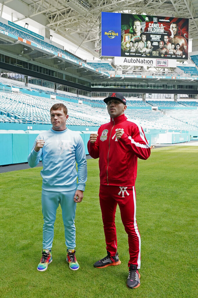 "Boxers Saul ""Canelo"" Alvarez, left, and Avni Yildirim pose for photos at Hard Rock Stadium, Monday, Feb. 22, 2021, in Miami Gardens, Fla. Alvarez will defend his WBC and WBA super-middleweight titles against Yildirim on Saturday. (AP Photo/Marta Lavandier)"