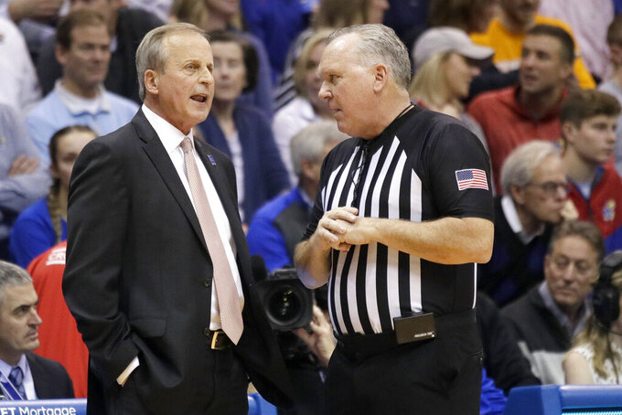 Tennessee head coach Rick Barnes, left, talks with referee James Luckie during the first half of an NCAA college basketball game against Kansas in Lawrence, Kan., Saturday, Jan. 25, 2020. (AP Photo/Orlin Wagner)
