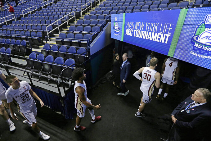 FILE - Florida State players leave the court after the NCAA college basketball games were canceled at the Atlantic Coast Conference tournament in Greensboro, N.C., in this Thursday, March 12, 2020, file photo. (AP Photo/Gerry Broome, File)