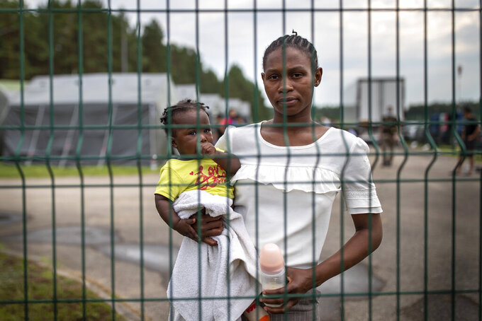 """Towe Mahawa, a migrants from Guinea, holds her daughter Kadaitou as she looks through a fence at the refugee camp in Druskininkai, some 145km (99,1 miles) south from Vilnius, Lithuania, Tuesday, July 13, 2021. Lithuania has struggled with a flow of migrants from the Middle East and Africa, a huge influx that officials in the tiny Baltic country say was organized by Belarusian authorities as part of a """"hybrid war"""" against the European Union.(AP Photo/Mindaugas Kulbis)"""