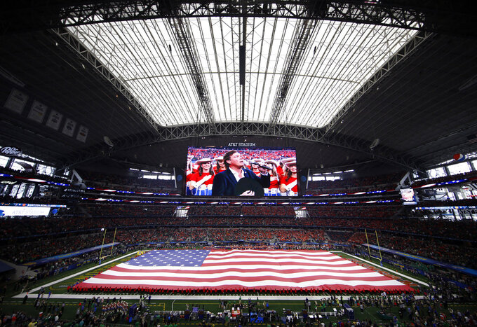 An American flag is displayed over the field as Clay Walker, on video screen, sings the national anthem before the NCAA Cotton Bowl semi-final playoff football game between Clemson and Notre Dame on Saturday, Dec. 29, 2018, in Arlington, Texas. (AP Photo/Roger Steinman)