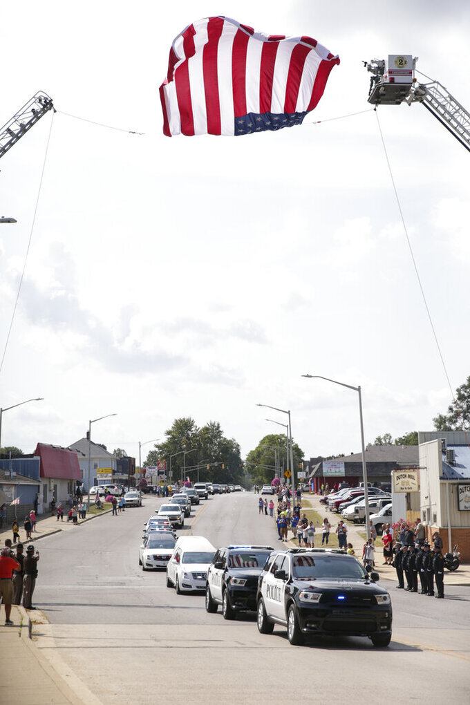 """The funeral procession for Marine Cpl. Humberto """"Bert"""" Sanchez passes under an American flag, Tuesday, Sept. 14, 2021 in Logansport, Ind. Sanchez was one of 13 U.S. service members to die in an explosion during evacuation efforts in Afghanistan. (Nikos Frazier/Journal & Courier via AP)"""