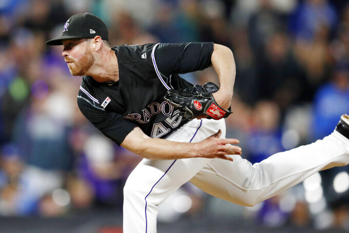 FILE - In this June 1, 2019, file photo, Colorado Rockies relief pitcher Scott Oberg follows through with a pitch against the Toronto Blue Jays during the ninth inning of a baseball game in Denver. Oberg is steadily making his way back to the mound after sitting out last season due to blood clots in his pitching arm. it was the third time over his career the clots have surfaced.  (AP Photo/David Zalubowski, File)