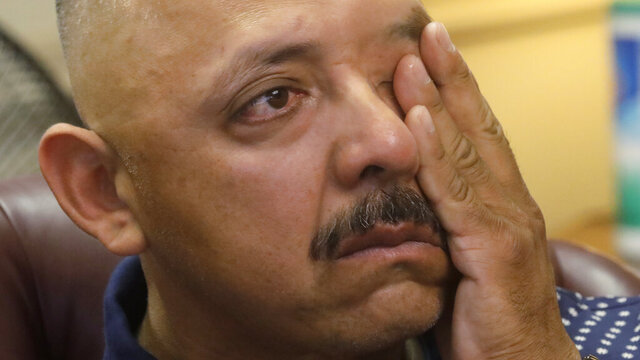 Jovany Mercado's father Juan wipes his face during a news conference at his attorney's office Thursday, July 23, 2020, in Salt Lake City. The parents of a Utah man who was shot and killed by police in his driveway while holding a knife have filed a lawsuit against the city of Ogden and its police department. In the lawsuit filed Wednesday, July 22, 2020. Juan and Rosa Mercado allege the officers had no reason to shoot their son because he posed no harm to the officers or anyone else and hadn't broken any laws. (AP Photo/Rick Bowmer)