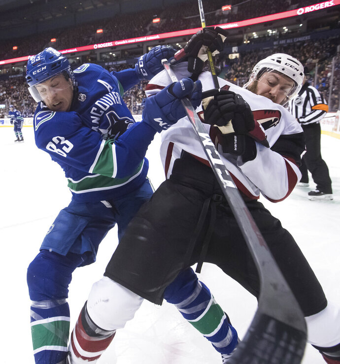 Vancouver Canucks' Jay Beagle, left, checks Arizona Coyotes' Derek Stepan during the first period of an NHL hockey game Thursday, Feb. 21, 2019, in Vancouver, British Columbia. (Darryl Dyck/The Canadian Press via AP)