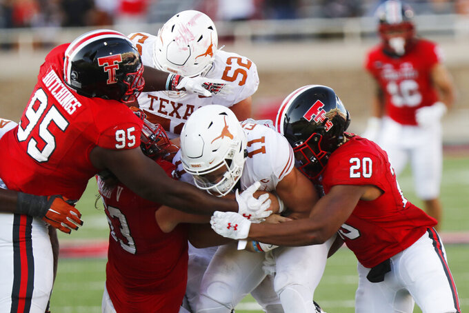 Texas Tech defensive lineman Jaylon Hutchings and linebacker Kosi Eldridge tackle Texas quarterback Sam Ehlinger during the second half of an NCAA college football game against Texas Tech, Saturday Sept. 26, 2020, in Lubbock, Texas. (AP Photo/Mark Rogers)