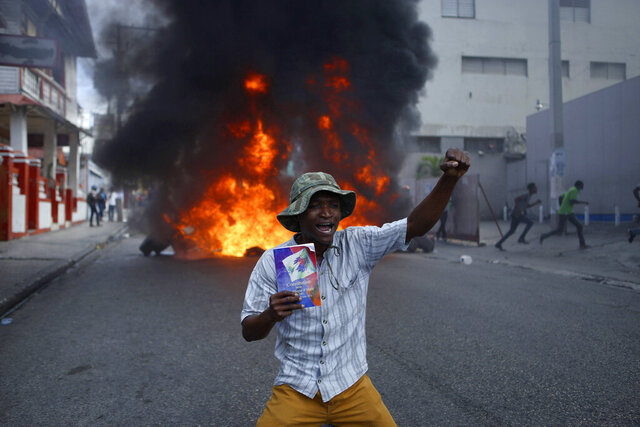 A protester kneels in front of a burning barricade with a copy of the Haitian Constitution during a demonstration demanding the resignation of President Jovenel Moise, in Port-au-Prince, Haiti, Friday, Jan. 15, 2021. Moise has one more year in power, but a growing groundswell of opposition is organizing protests and demanding he resign next month amid spiraling crime, a crumbling economy and approval of what critics say are illegal presidential decrees and unconstitutional moves, worrying many that Moïse is amassing too much power as he enters his second year of rule by decree. (AP Photo / Joseph Odelyn)