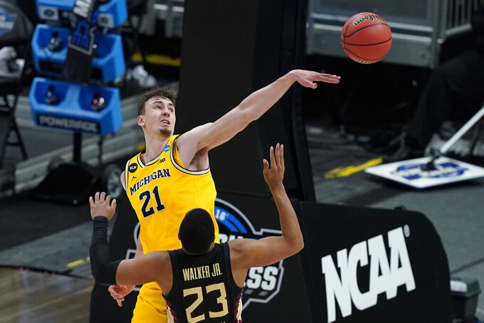 Michigan guard Franz Wagner (21) blocks a shot by Florida State guard M.J. Walker (23) during the second half of a Sweet 16 game in the NCAA men's college basketball tournament at Bankers Life Fieldhouse, Sunday, March 28, 2021, in Indianapolis. Michigan won 76-58. (AP Photo/Darron Cummings)