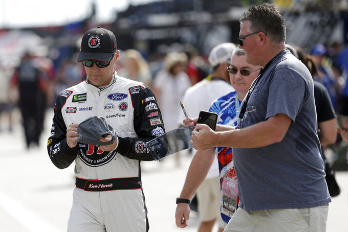 Kevin Harvick signs autographs during practice for Sunday's NASCAR Cup Series auto race at Charlotte Motor Speedway in Concord, N.C., Saturday, Sept. 28, 2019. (AP Photo/Gerry Broome)