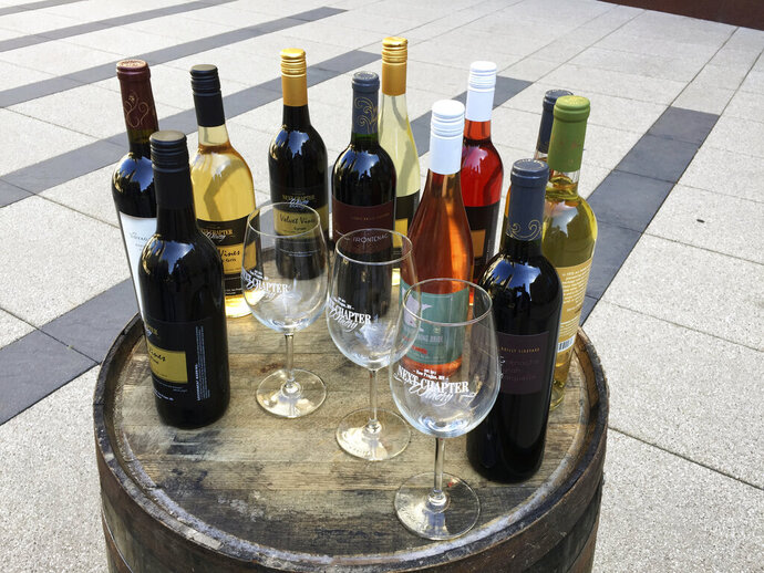 FILE - In the March 28, 2017, file photo, wines from the Next Chapter Winery, of New Prague, Minn., and Alexis Bailly Vineyard, of Hastings, Minn., are displayed at a news conference outside the federal courthouse in Minneapolis. A federal judge struck down a Minnesota law Monday, Aug. 31, 2020, that required wineries in the frosty state to use mostly Minnesota-grown grapes, in a ruling that could have implications for other cold-climate wine-producing states. (AP Photo/Steve Karnowski, File)