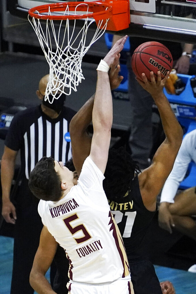 Florida State center Balsa Koprivica (5) fouls Colorado forward Evan Battey (21) during the second half of a second-round game in the NCAA college basketball tournament at Farmers Coliseum in Indianapolis, Monday, March 22, 2021. (AP Photo/Charles Rex Arbogast)