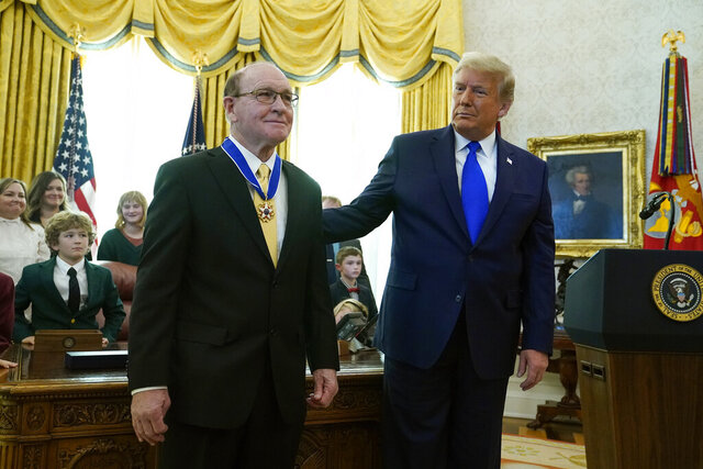 President Donald Trump congratulates Olympic gold medalist and former University of Iowa wrestling coach Dan Gable after awarding him the Presidential Medal of Freedom, the highest civilian honor, in the Oval Office of the White House, Monday, Dec. 7, 2020, in Washington. (AP Photo/Patrick Semansky)