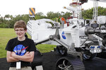 Alexander Mather, of Burke, Va. stands next to a model of the Mars 2020 rover he named in a contest during a news conference at the Kennedy Space Center Tuesday, July 28, 2020, in Cape Canaveral, Fla. Mather, submitted the winning entry in NASA's