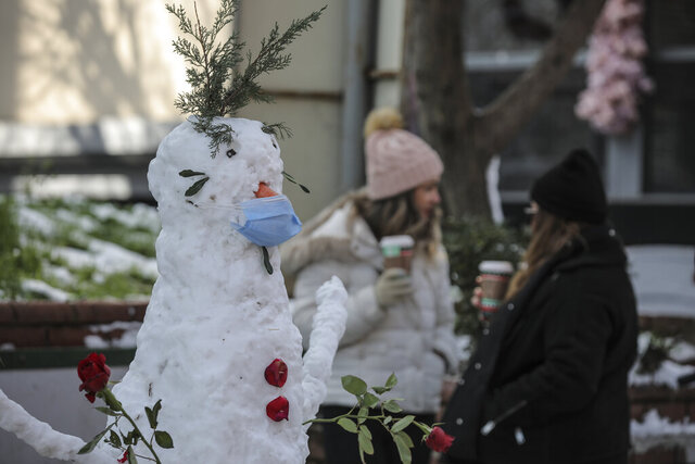 A snowman, featuring a mask, is seen in Istanbul, Monday, Jan 18, 2021. Snow blanketed most of the Turkish metropolis of some 16 million that spans two continents, bridging Europe to Asia and the flurries are forecasted to continue throughout the day. (AP Photo/Emrah Gurel)