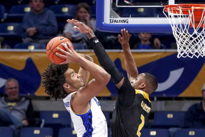 Pittsburgh's Justin Champagnie, left, shots as Arkansas-Pine Bluff's Marquell Carter (2) defends during the first half of an NCAA college basketball game Thursday, Nov. 21, 2019, in Pittsburgh. (AP Photo/Keith Srakocic)
