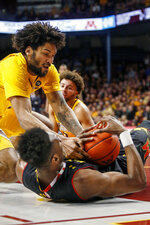 Minnesota's Jordan Murphy, left, grabs for the ball from Maryland's Bruno Fernando and results in a jump ball during an NCAA college basketball game Tuesday, Jan. 8, 2019, in Minneapolis. (AP Photo/Bruce Kluckhohn)