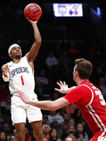 Richmond guard Blake Francis (1) shoots as Wisconsin forward Nate Reuvers (35) defends during the second half of an NCAA college basketball game in the Legends Classic, Monday, Nov. 25, 2019, in New York. Richmond defeated Wisconsin 62-52. (AP Photo/Kathy Willens)