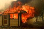 A firefighter battles the Morton Fire as it consumes a home near Bundanoon, New South Wales, Australia, Thursday, Jan. 23, 2020. (AP Photo (AP Photo/Noah Berger)