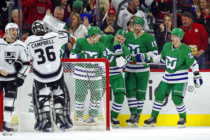 Carolina Hurricanes' Nino Niederreiter (21), of Switzerland, celebrates his goal against the Los Angeles Kings with teammates Teuvo Teravainen (86), of Finland, Dougie Hamilton (19) and Sebastian Aho (20), also of Finland, during the first period of an NHL hockey game in Raleigh, N.C., Saturday, Jan. 11, 2020. (AP Photo/Karl B DeBlaker)