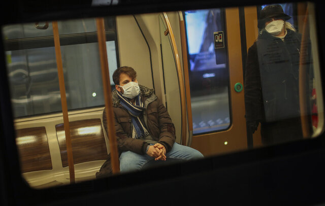 People wearing face masks travel by metro in Brussels, Wednesday, March 18, 2020. Belgium has ordered further lockdown measures starting Wednesday, following in the steps of European neighbours Italy, Spain and France. For most people, the new coronavirus causes only mild or moderate symptoms, such as fever and cough. For some, especially older adults and people with existing health problems, it can cause more severe illness, including pneumonia. (AP Photo/Francisco Seco)