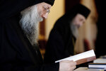 A Bishop reads before a meeting with the head of Cyprus Orthodox Church Archbishop Chrysostomos II, who presides over, composing the Holy Synod, the Church's highest decision-making body at the Church's headquarters in the capital Nicosia, Cyprus, on Monday, Nov. 23, 2020. The Holy Synod convened to discuss issues relating to the Cyprus Church's position on the independence of the Ukrainian Orthodox Church. (AP Photo/Petros Karadjias)