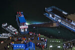 In this photo released by Xinhua News Agency, rescuers conduct search and rescue at the site of an overturned passenger ship in Liupanshui in southwest China's Guizhou province, Sunday, Sept. 19, 2021. The boat has left multiple people dead, with several others still missing, according to state media on Sunday. CCTV said that the ship overturned shortly after it departed Saturday evening. Preliminary investigations suggest that the ship was blown over by strong winds. (Ou Dongqu/Xinhua via AP)