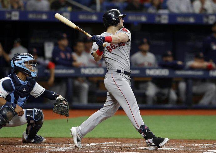 Boston Red Sox's Andrew Benintendi follows the flight of his grand slam off Tampa Bay Rays starting pitcher Charlie Morton during the second inning of a baseball game Saturday, April 20, 2019, in St. Petersburg, Fla. Catching for the Rays is Michael Perez. (AP Photo/Chris O'Meara)