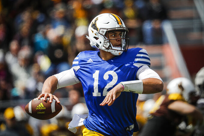 In this Saturday, April 13, 2019, photo, Wyoming quarterback Sean Chambers (12) winds up for a throw during a NCAA college football spring scrimmage in Casper, Wyo. Wyoming plays Missouri on Saturday. (Josh Galemore/The Casper Star-Tribune via AP)