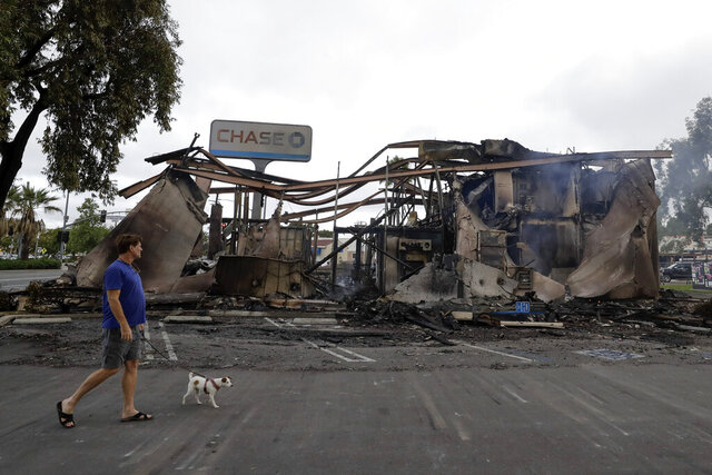 A man passes a bank burned during a protest over the death of George Floyd, Sunday, May 31, 2020, in La Mesa, Calif. Protests were held in U.S. cities over the death of Floyd, a black man who died after being restrained by Minneapolis police officers on May 25. (AP Photo/Gregory Bull)