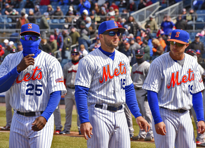 Tim Tebow, center, stands with Syracuse Mets teammates before a Triple-A baseball game against the Pawtucket Red Sox in Syracuse, N.Y., Thursday, April 4, 2019. The former NFL quarterback and Heisman Trophy winner went 0 for 4 for the top minor league affiliate of the New York Mets. He wasn't available for comment after the Syracuse Mets lost to the Pawtucket Red Sox 6-3 in 10 innings. (Michael Greenlar/The Post-Standard via AP)