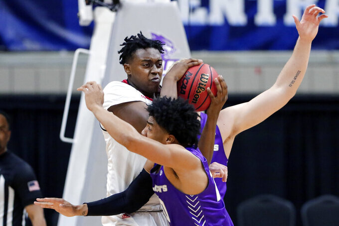 Nicholls State center Ryghe Lyons, back, protects the ball from the lunge by Abilene Christian guard Coryon Mason, front, during the first half of an NCAA college basketball game for the Southland Conference men's tournament championship Saturday, March 13, 2021, in Katy, Texas. (AP Photo/Michael Wyke)