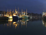 In this Nov. 3, 2018 photo fishing boats are seen at dusk in Newport, Ore. A commercial crabbing boat capsized in rough waters as it crossed Yaquina Bay bar in Newport, Tuesday night, Jan. 8, 2019, killing the three men aboard and sending a shock wave through the seafaring community. (AP Photo/Andrew Selsky)