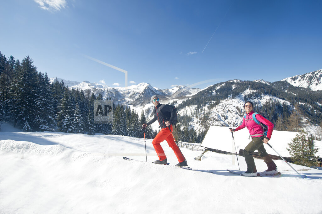 Young man and woman skiing on snow