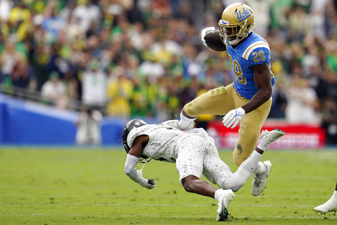 UCLA running back Brittain Brown (28) leaps over an Oregon defender during the first half of an NCAA college football game Saturday, Oct. 23, 2021, in Pasadena, Calif. (AP Photo/Marcio Jose Sanchez)