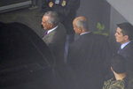 In this photo shot through a fence, former Brazilian President Michel Temer, left, is seen at the international airport in Sao Paulo, Brazil, Thursday, March 21, 2019. In a statement, the Prosecutors Office in Rio de Janeiro said that Judge Marcelo Breitas had issued an arrest warrant for Temer, as well as Moreira Franco, a former minister and close ally of Temer, and eight others. (AP Photo/Nelson Antoine)