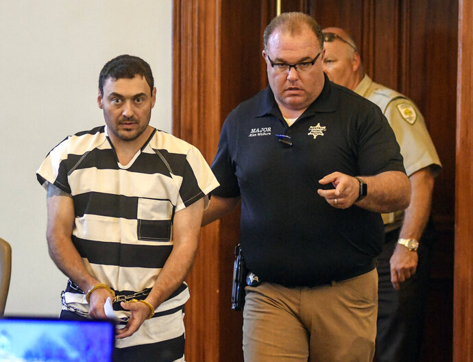 Oxford Police Officer Matthew Kinne, center, is escorted into a hearing by Lafayette County Sheriff Dept. Maj. Alan Wilburn at the Lafayette County Courthouse, Wednesday, May 22, 2019, in Oxford, Miss. Kinne is charged in the death of 32-year-old Dominique Clayton, who was found dead Sunday. (Bruce Newman/The Oxford Eagle via AP)