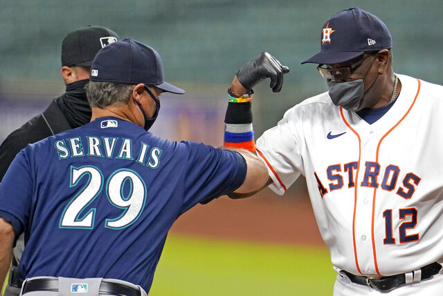 Houston Astros' Dusty Baker (12) bumps elbows with Seattle Mariners manager Scott Servais (29) before a baseball game Saturday, July 25, 2020, in Houston. (AP Photo/David J. Phillip)