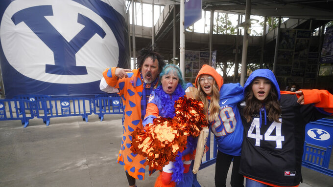 Boise State fans, from left, Jason and Selena Jungling, Lillian McAlister and Macy Kile show their support for their team before an NCAA college football game against BYU Saturday, Oct. 9, 2021, in Provo, Utah. (AP Photo/Rick Bowmer)