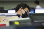 A currency trader watches monitor at the foreign exchange dealing room of the KEB Hana Bank headquarters in Seoul, South Korea, Wednesday, Feb. 26, 2020. Asian shares slid Wednesday following another sharp fall on Wall Street as fears spread that the growing virus outbreak will put the brakes on the global economy.(AP Photo/Ahn Young-joon)