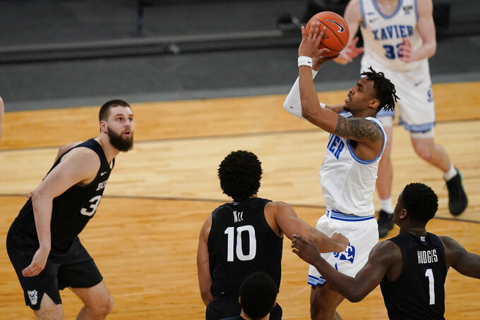 Xavier's Paul Scruggs shoots over Butler's Bryce Nze (10), Bo Hodges (1) and Bryce Golden during the overtime period of an NCAA college basketball game in the Big East conference tournament Wednesday, March 10, 2021, in New York. (AP Photo/Frank Franklin II)
