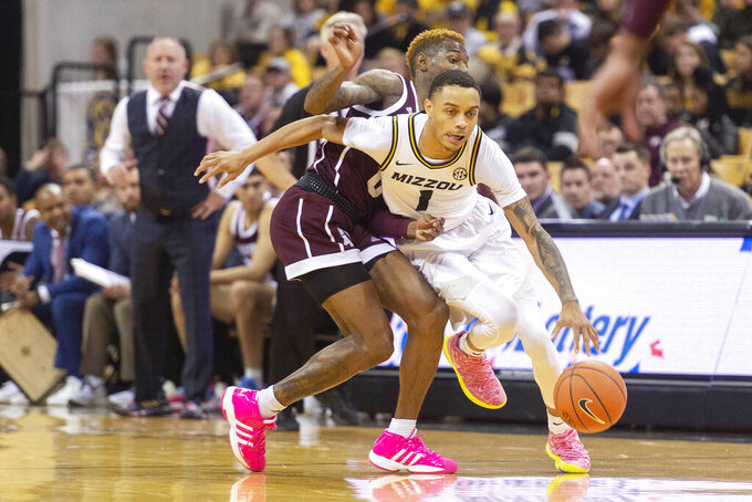 Missouri's Xavier Pinson, right, dribbles around Texas A&M's Jay Jay Chandler, left, during the second half of an NCAA college basketball game Tuesday, Jan. 21, 2020, in Columbia, Mo. Texas A&M won the game 66-64. (AP Photo/L.G. Patterson)