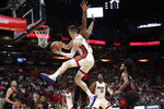 Miami Heat guard Tyler Herro (14) passes around Chicago Bulls center Wendell Carter Jr., center, during overtime in an NBA basketball game, Sunday, Dec. 8, 2019, in Miami. The Heat won 110-105 in overtime. (AP Photo/Lynne Sladky)