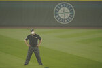 Second base umpire Bill Miller wears a mask as he stands on the field in air hazy from wildfire smoke during the first baseball game of a doubleheader between the Seattle Mariners and the Oakland Athletics, Monday, Sept. 14, 2020, in Seattle. (AP Photo/Ted S. Warren)
