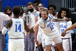 UCLA's Mac Etienne (12) slaps hands with Kenneth Nwuba (14) in the final moments of their 67-47 win over Abilene Christian in a college basketball game in the second round of the NCAA tournament at Bankers Life Fieldhouse in Indianapolis Monday, March 22, 2021. (AP Photo/Mark Humphrey)