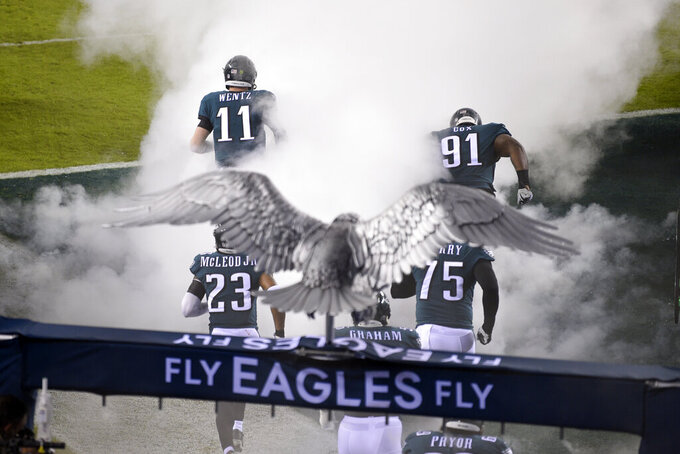Philadelphia Eagles' Carson Wentz (11) and Fletcher Cox (91) run onto the field before an NFL football game against the Seattle Seahawks, Monday, Nov. 30, 2020, in Philadelphia. (AP Photo/Derik Hamilton)